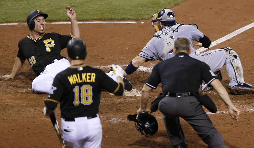 Pittsburgh Pirates' Travis Ishikawa, left, scores on a hit by Gregory Polanco as San Diego Padres catcher Derek Norris reaches to tag him in the eighth inning of a baseball game, Wednesday, July 8, 2015, in Pittsburgh. Neil Walker (18) and home plate umpire Jim Wolf watch.(AP Photo/Keith Srakocic)