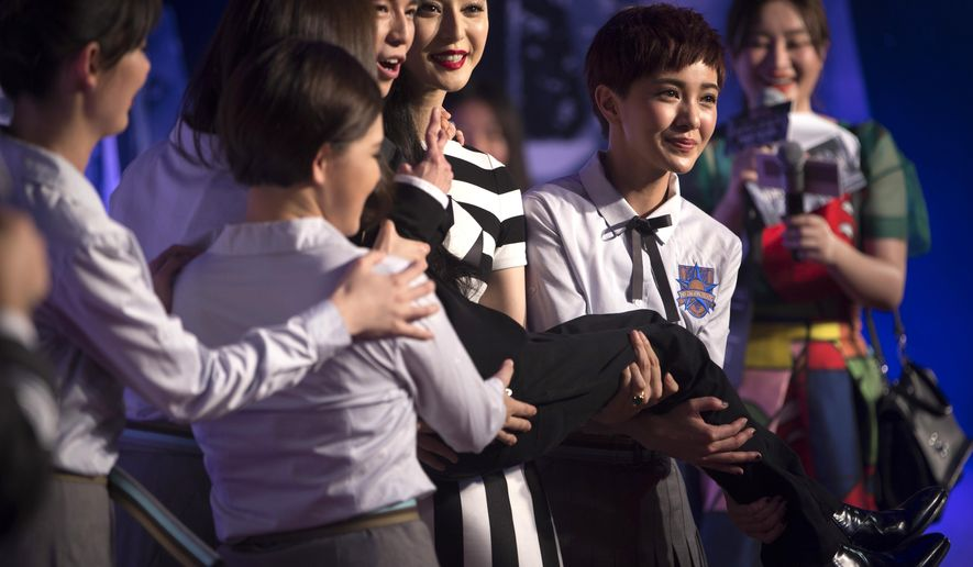 """Chinese actress Fan Bingbing, center, and Taiwanese actress Guo Caijie (Amber Kuo), right, hold Chinese director Guo Jingming as they pose for photos at a red carpet event for the premiere of the movie """"Tiny Times 4"""" in Beijing, Wednesday, July 8, 2015. Stars attended the premiere of the expected final installment of one of China's most successful movie franchises, whose depiction of the lives and loves of four young women has garnered many fans among the young cinema-going audience. (AP Photo/Mark Schiefelbein)"""