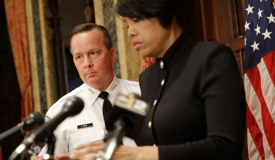Interim Baltimore Police Department Commissioner Kevin Davis, left, follows Baltimore Mayor Stephanie Rawlings-Blake into a news conference, Wednesday, July 8, 2015, in Baltimore, to announce her firing of Commissioner Anthony Batts. (AP Photo/Patrick Semansky)