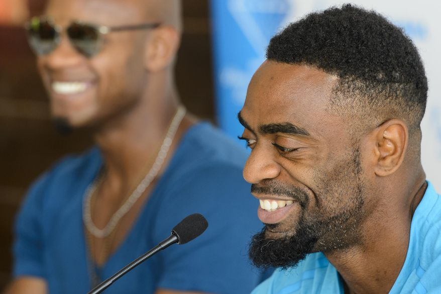 Asafa Powell, from Jamaica, left, and Tyson Gay, from the USA, right,  attend a news conference on the eve of the Athletissima international Athletics meeting, in Lausanne, Switzerland, Wednesday, July 8, 2015. ( (Jean-Christophe Bottt/Keystone via AP)