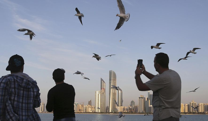 FILE - In this Wednesday Jan. 14, 2015 file photo, a man takes a photo with his mobile phone as others throw potato chips toward seagulls in front of city skyline in Abu Dhabi, United Arab Emirates. The U.S. and Emirati governments said they have launched a new digital communications center focused on using social media to counter the Islamic State group's active online propaganda efforts. The new Sawab Center, based in Abu Dhabi, became operational Wednesday, July 8. (AP Photo/Kamran Jebreili, file)