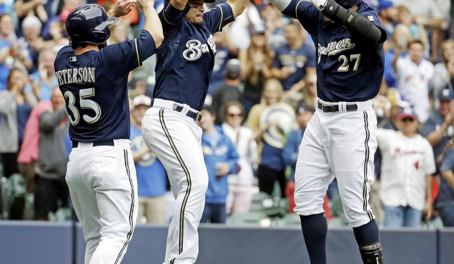 Milwaukee Brewers' Carlos Gomez celebrates his three-run home run with teammates Shane Peterson and Gerardo Parra during the eighth inning of a baseball game against the Atlanta Braves Wednesday, July 8, 2015, in Milwaukee. (AP Photo/Morry Gash)
