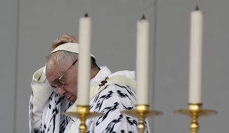Pope Francis adjusts his skull cap as he celebrates Mass at Bicentennial Park in Quito, Ecuador, Tuesday, July 7, 2015. Pope Francis used his final Mass in Ecuador to issue an appeal for the missionary church that he has championed. (AP Photo/Gregorio Borgia)