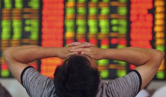 An investor covers his eyes at a brokerage house in Fuyang in central China's Anhui province on Wednesday. (Associated Press)