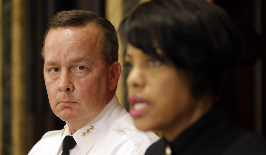 Interim Baltimore Police Department Commissioner Kevin Davis, left, listens to Mayor Stephanie Rawlings-Blake at a news conference, Wednesday, July 8, 2015, in Baltimore. Rawlings-Blake announced that she fired Commissioner Anthony Batts. (AP Photo/Patrick Semansky)