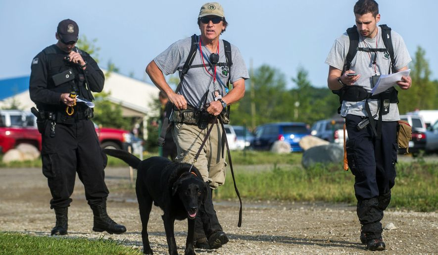 A trio of search and rescue officials walk towards a wooded area with a trained dog during a search for 9-year-old Omarion Humphrey, Wednesday, July 8, 2015, in Davison Township, Mich. Authorities are using lights and music as part of their efforts to find Humphrey, who is autistic, last seen at the Flint, Mich., area park on Saturday night. (Jake May/The Flint Journal-MLive.com via AP)