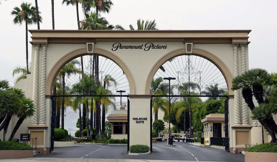 "The main gate to Paramount Studios is seen on Melrose Avenue, Wednesday, July 8, 2015, in Los Angeles. Paramount Pictures chiseled a crack into the closely guarded theatrical window on Wednesday, July 8, 2015, in an experimental agreement with two leading theater chains that will trim the length of time a handful of movies are restricted to playing only in theaters. Paramount, along with AMC Theaters and Cineplex Entertainment, announced a deal to shorten the rollout of two low-budget horror films due out in October: Paramount's ""Paranormal Activity: The Ghost Dimension"" and ""Scout's Guide to the Zombie Apocalypse."" (AP Photo/Nick Ut)"