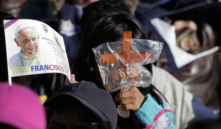 A girl uses two small wooden crosses as sun shades to protect herself from the glare of the morning sun as she waits for the arrival of Pope Francis outside the National Shrine of Our Lady of the Presentation of El Quinche, in El Quinche, Ecuador, Wednesday, July 8, 2015. Francis wraps up the first leg of a three-nation South American pilgrimage Wednesday. Next stop on the pope's South American tour is La Paz, Bolivia, where he will be welcomed by President Evo Morales. (AP Photo/Ana Buitron)