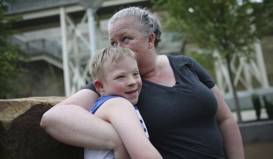 In this Tuesday, July 7, 2015 photo, Steven Heffron, 6, and his mother, Denise Watts, hug in Smale Riverfront Park in downtown Cincinnati. Watts has filed a federal lawsuit alleging discrimination, saying an Ohio YMCA excluded her son from summer camp because he has Down syndrome and treated him hypocritically after using him in promotions extolling opportunities for everyone. (AP Photo/John Minchillo)