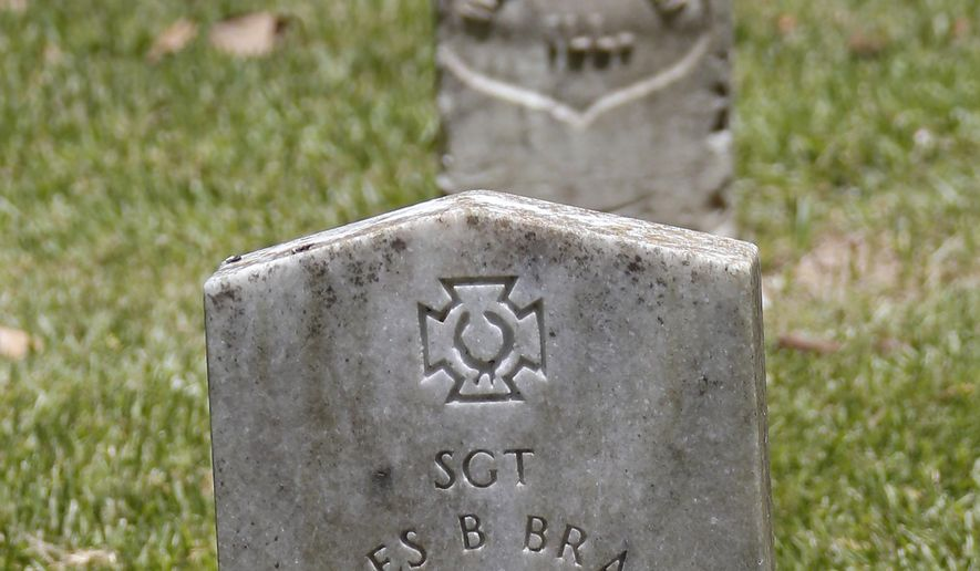 Two small faded Confederate battle flags flank the grave marker of Confederate soldier Sgt. Charles B. Brantley, who along with Private Reuben H. White are the only Confederate fighters buried in Vicksburg National Military Park in Vicksburg, Miss., Thursday, July 9, 2015. The Republican-controlled House scrapped a vote on permitting the Confederate flag at Park Service-run cemeteries on Thursday, a retreat under fire that only escalated a ferocious attack by Democrats complaining the banner celebrates a murderous, racist past. (AP Photo/Rogelio V. Solis)