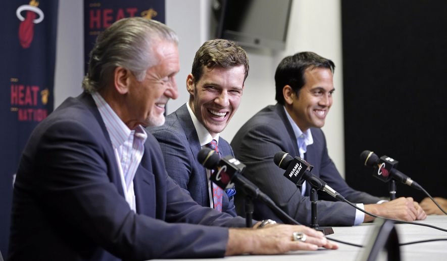 Miami Heat's Goran Dragic, center, laughs at a comment by Miami Heat president Pat Riley, left, as head coach Erik Spoelstra, right,  smiles during a news conference, Thursday, July 9, 2015, in Miami. Goran Dragic has signed a five-year deal with the Miami Heat.  (AP Photo/Alan Diaz)