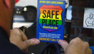"""In this June 24, 2015, photo, Officer Jim Ritter places a """"Safe Place"""" sticker on the window of a business in Seattle's Capitol Hill neighborhood. Last September, after more than three decades on the force, Ritter, 54, was appointed as SPD's first full-time liaison to the city's LGBTQ community. (Ellen M. Banner(/The Seattle Times via AP)"""