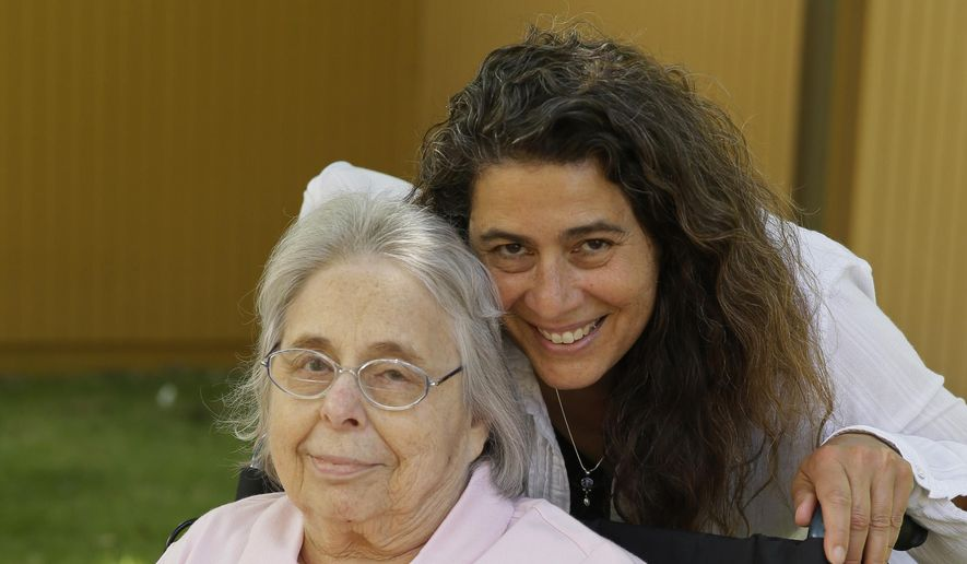 Kamila Al-Najjar poses with her mother, Joan Groen, at her assisted living facility in Santa Rosa, Calif., on Monday July 6, 2015. Caught between kids and aging parents, a new poll shows the sandwich generation worries more than most Americans their age about how they'll afford their own care as they grow older.  (AP Photo/Eric Risberg)