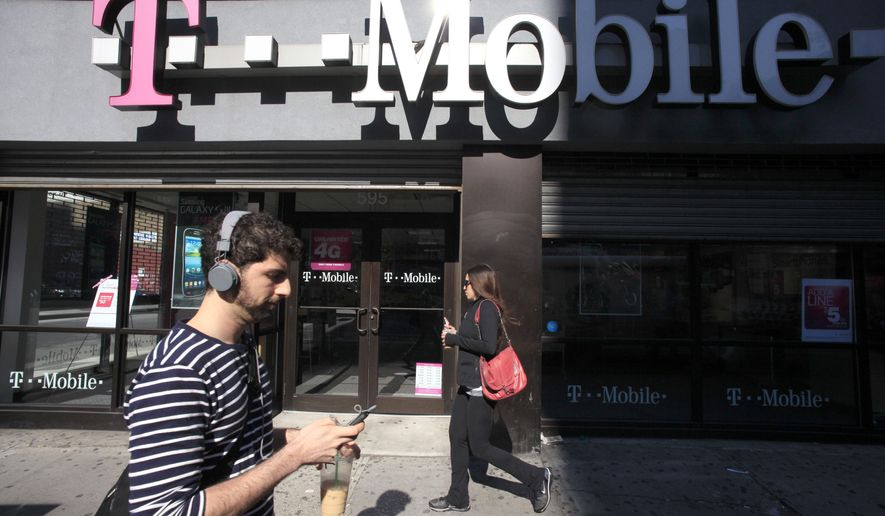 A man uses a cellphone as he passes a T-Mobile store in New York. (AP Photo/Mark Lennihan, File)