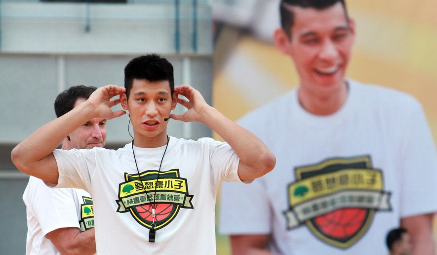 Former Los Angeles Lakers'  Jeremy Lin holds a short basketball clinic with young Taiwanese players in Taipei, Taiwan, Saturday, July 4, 2015. Lin is in Taiwan to attend a charity event and basketball clinics for young athletes. (AP Photo/Chiang Ying-ying)