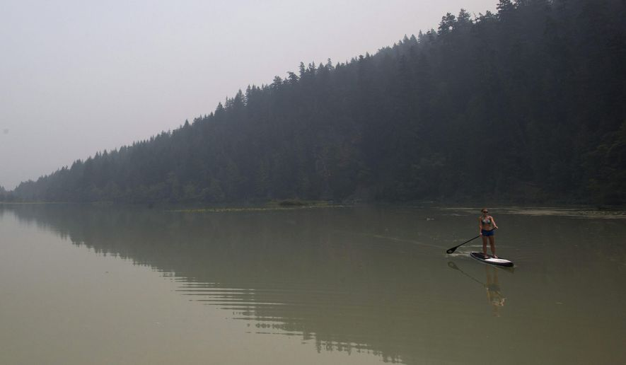 Smoke from wildfires fills the air as Lisa Fogarty paddleboards at One Mile Lake in Pemberton, in Pemberton, British Columbia, Wednesday, July 8, 2015. Firefighters made some progress Wednesday in quelling hundreds of wildfires raging across central and western Canada that are threatening thousands of people and triggering air quality warnings across the country and in the U.S. West and Midwest, authorities said. (Darryl Dyck/The Canadian Press via AP) MANDATORY CREDIT