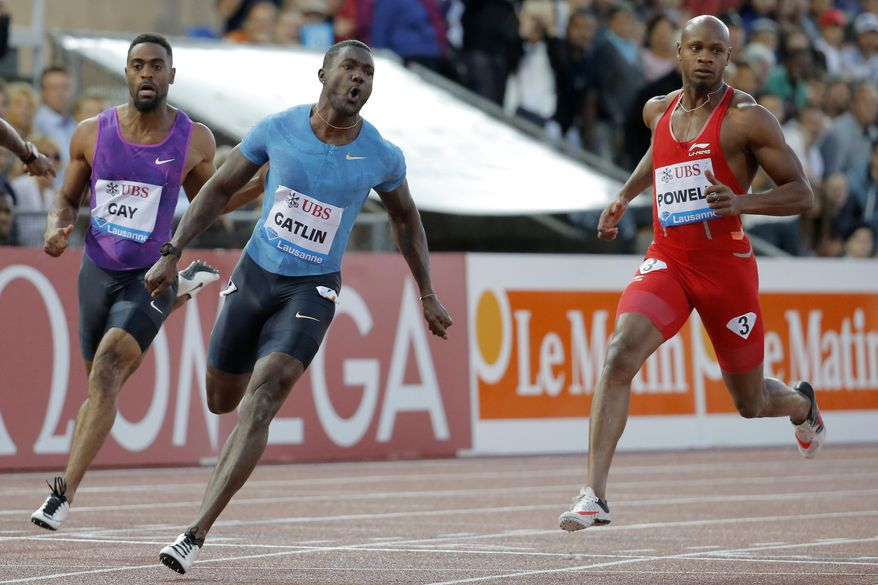 From left, Tyson Gay from the USA, Justin Gatlin from the USA and Asafa Powell from Jamaica compete in the men's 100m race at the Athletissima IAAF Diamond League athletics meeting in the Stade Olympique de la Pontaise in Lausanne, Switzerland, Thursday, July 9, 2015. (Valentin Flauraud/Keystone via AP)