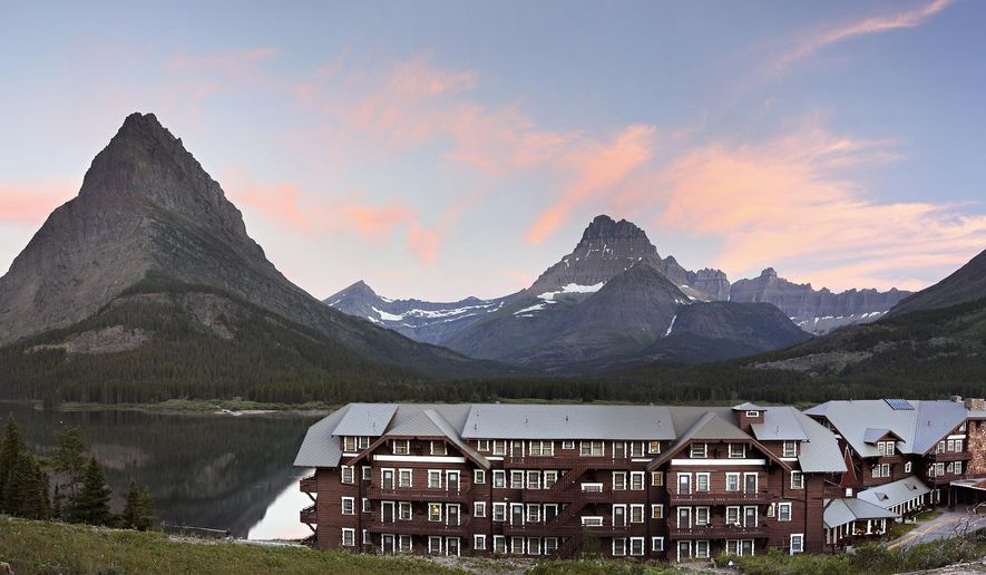 This July 3, 2015 photo shows the sunrise over Many Glacier Hotel on Glacier National Park, Mont. This summer, the Many Glacier Hotel celebrates 100 years as one of the crown jewels of Glacier National Park. For more than a century, the massive hotel has withstood the ravages of time, floods and fire, all the while enticing people with its legend and lore. (Greg Lindstrom/Flathead Beacon via AP)