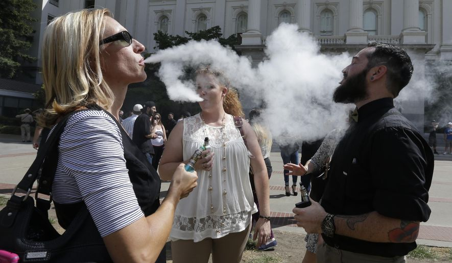 Kari Hess, left, co-owner of Nor Cal Vape, in Redding, Calif., celebrates with Jackie Voisione, center, and Michael Ventura, right, an e-liquid manufacturer from San Diego, after a bill to regulate E-Cigarettes stalled in an Assembly Committee, at the Capitol Wednesday, July 8, 2015, in Sacramento, Calif.(AP Photo/Rich Pedroncelli)