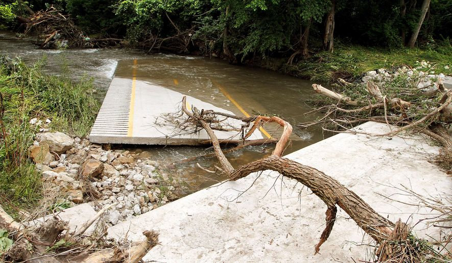 In this Wednesday, July 8, 2015 photo, debris is scattered near a section of the pedestrian and bike path after recent heavy rainfall into Crow Creek washed out a small bridge at Crow Creek Park in Bettendorf, Iowa. (Kevin E. Schmidt/The Quad City Times via AP)