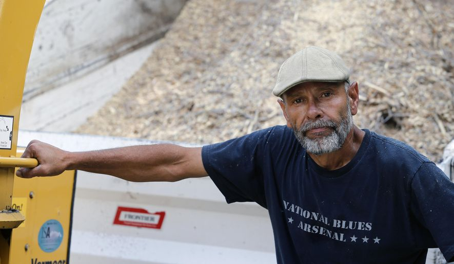 Alejandro Menocal, 53, a legal permanent resident in the United States who emigrated from Mexico in 1973, stands near one of the machines he operates as an employee of a tree trimming business, in Golden, Colo, Thursday, July 9, 2015. Menocal is one of a group of immigrants who were detained at a suburban Denver facility who are filing a lawsuit against GEO, the private company that held them, alleging that they were paid $1 a day to do janitorial work, sometimes under threat of solitary confinement. (AP Photo/Brennan Linsley)