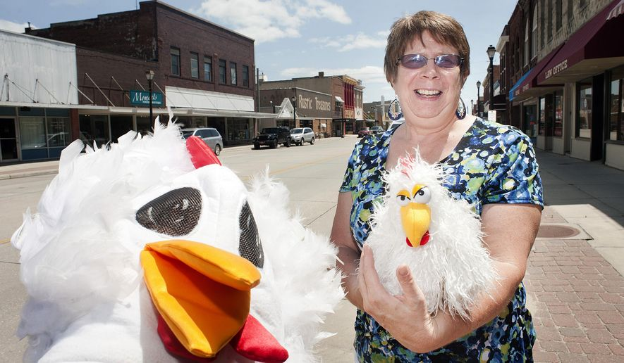 In this Monday, June 22, 2015 photo, Irene Fletcher, assistant director at Wayne Area Economic Development, poses for a photo with a chicken mascot costume in Wayne, Neb. The Chicken Show will go on in Wayne, despite the continuing worries about avian flu. (Justin Wan/The Sioux City Journal via AP)