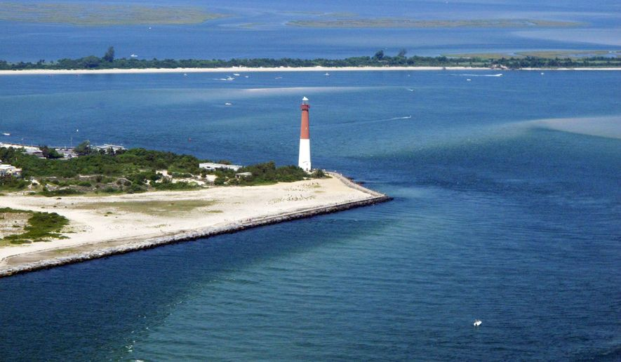 This July 11, 2014 aerial photo shows the Barnegat Lighthouse in Barnegat Light, N.J., part of Long Beach Island. A seismic testing that blasted the ocean floor off Long Beach Island with sound waves to study climate change was completed on July 6, 2015. The research was bitterly opposed by environmentalists and fishing groups who say it can harm marine life including dolphins, whales and turtles. (AP Photo/Wayne Parry)