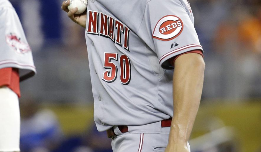 Cincinnati Reds starting pitcher Michael Lorenzen wipes his face after hitting Miami Marlins' Derek Dietrich with a pitch during the first inning of a baseball game, Thursday, July 9, 2015, in Miami. (AP Photo/Lynne Sladky)