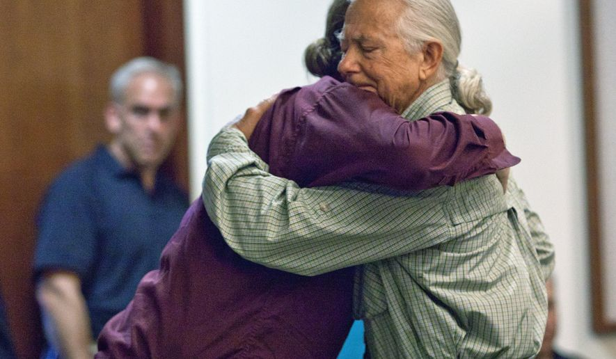 Joel Battaglia's brother, Jeremy Battaglia, left, and father, Jerry Battaglia, hug after Jerry gave a statement during Aurelias Marshall's sentencing at the Kent County Courthouse in Grand Rapids, Mich., Thursday, July 9, 2015. Marshall received life in prison without possibility of parole for the 1990 murder of Joel Battaglia. (Cory Morse/The Grand Rapids Press via AP)