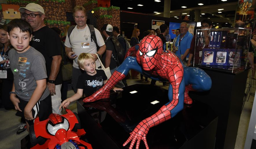 Fans walk past a Spiderman display on Preview Night at the 2015 Comic-Con International held at the San Diego Convention Center Wednesday, July 8, 2015, in San Diego. The pop-culture event runs July 9-12. (Photo by Denis Poroy/Invision/AP)
