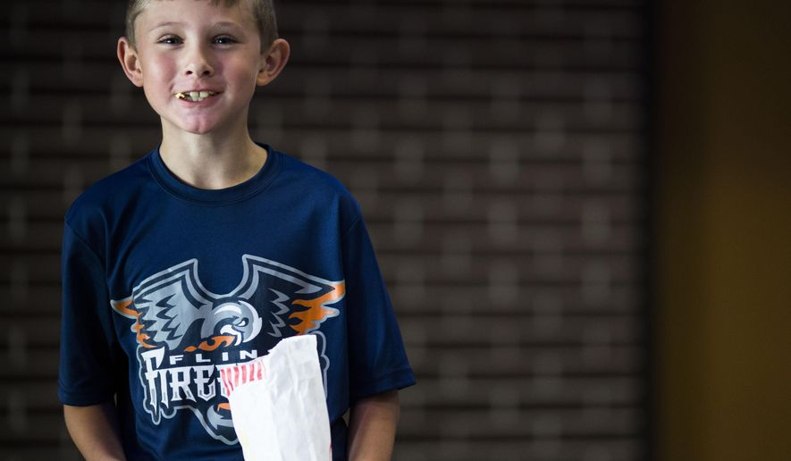 Kiefer Ward, 8, an avid hockey fan and aspiring athlete, poses for a portrait during a news conference where Dort Federal Credit Union Event Center was announced as the new name for Perani Arena Thursday, July 9, 2015, in Flint, Mich. (Danny Miller/The Flint Journal-MLive.com via AP) LOCAL TELEVISION OUT; LOCAL INTERNET OUT; MANDATORY CREDIT