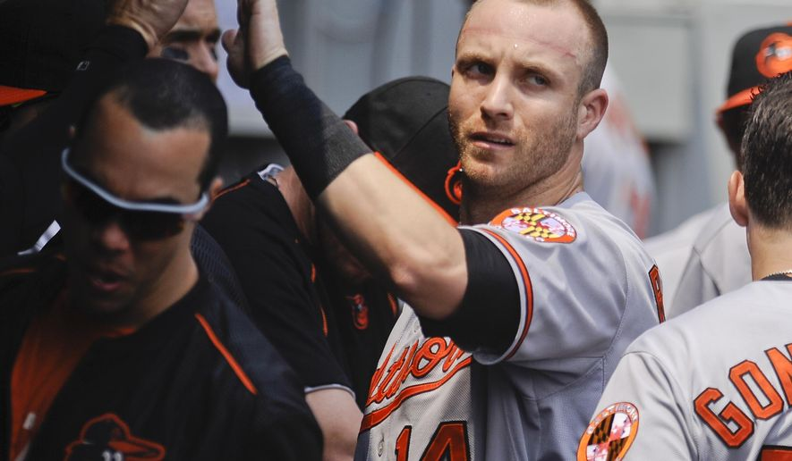 Baltimore Orioles' Nolan Reimold celebrates in the dugout after he scored on an RBI-double by Adam Jones during the first inning of a baseball game against the Chicago White Sox in Chicago on Sunday, July 5, 2015. (AP Photo/Matt Marton)