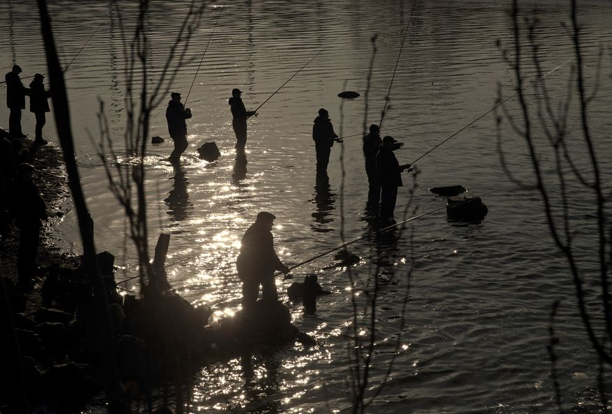 People fish in a stream outside a steel factory in the Sea of Azov port city, Mariupol, Ukraine, Tuesday, March 10, 2015. The bulk of continued unrest along the 485-kilometer (300-mile) front lines, between Ukraine's government forces and Russia-backed rebels, has been concentrated around the separatist stronghold of Donetsk, but pitched battles are also taking place in the town of Shyrokyne, near the strategic port city of Mariupol. (AP Photo/Vadim Ghirda)