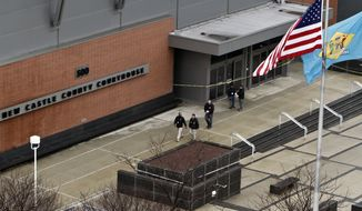 In this Feb. 11, 2013, file photo, law enforcement officials and investigators gather outside the New Castle County Courthouse in Wilmington, Del., after three people died in a shooting at a courthouse, including the shooter. A federal judge on Tuesday, June 9, 2015, rejected a prosecution request to keep the names of jurors secret in the cyberstalking trial of the widow and children of Thomas Matusiewicz, who killed his former daughter-in-law, a friend and exchanged gunfire with police before killing himself at the courthouse. (AP Photo/Joseph Kaczmarek, File)