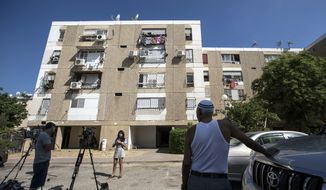Israeli journalists report outside the apartment building of Ethiopian-Israeli Avraham Mengisto, 28, in the coastal city of Ashkelon, Israel, Thursday, July 9, 2015. An Israeli security official said Thursday the Hamas militant group has been holding Mengisto in the Gaza Strip for nearly a year. (AP Photo/Tsafrir Abayov)