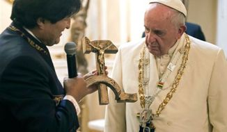 Pope Francis is presented with a gift of a crucifix carved into a wooden hammer and sickle, the Communist symbol uniting labor and peasants, by Bolivian President Evo Morales in La Paz, Bolivia, Wednesday, July 8, 2015.  (L'Osservatore Romano/Pool Photo via AP) ** FILE **