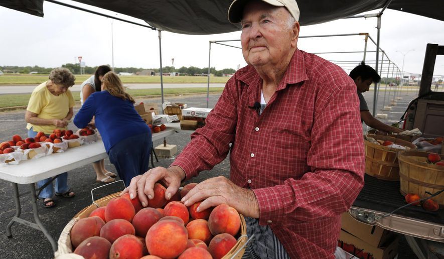 In this Wednesday, July 8, 2015 photo, John Doak, a longtime Montague County peach grower, sells his produce at Cowtown Farmers Market in Fort Worth, Texas. Some Texas growers, including Doak, are expecting a plentiful peach harvest in spite of heavy spring rain and flooding that left some fields impassable. (David Kent/The Fort Worth Star-Telegram via AP)