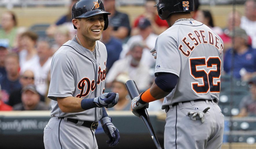 Detroit Tigers' Ian Kinsler, left, is congratulated by Yoenis Cespedes after Kinsler's solo home run off Minnesota Twins starting pitcher Mike Pelfrey during the first inning of a baseball game in Minneapolis, Thursday, July 9, 2015. (AP Photo/Ann Heisenfelt)