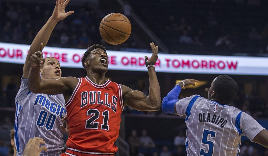 FILE - In this Feb. 8, 2015, file photo, Chicago Bulls guard Jimmy Butler (21) fights for the ball with Orlando Magic forward Aaron Gordon (00) and Magic guard Victor Oladipo (5) during the first half of an NBA basketball game, in Orlando, Fla. The Chicago Bulls are set to announce a maximum contract for All-Star guard Jimmy Butler. The team has scheduled a news conference for Thursday, July 9, 2015, the first day deals can be announced. (AP Photo/Willie J. Allen Jr., File)