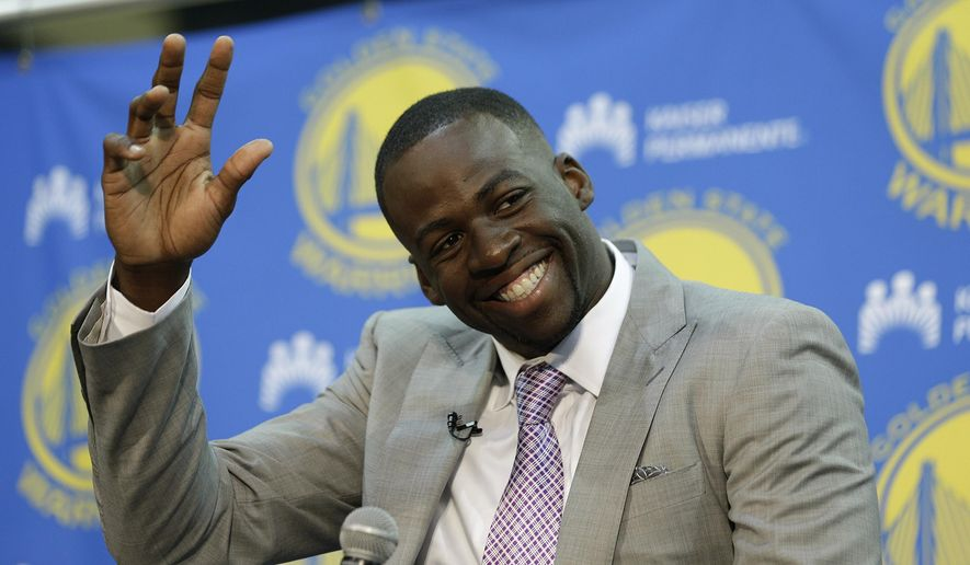 Golden State Warriors forward Draymond Green waves to a group of children at the start of a news conference Thursday, July 9, 2015, in Oakland, Calif. The Warriors announced they re-signed Green to a multi-year contract. (AP Photo/Eric Risberg)