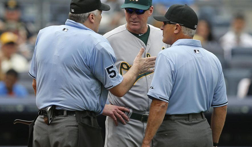 Oakland Athletics manager Bob Melvin, center, talks with home plate umpire Bill Welke (52) and crew chief John Hirschbeck, right, questioning whether Cole Figueroa's fourth-inning ground ball double hopped fair or foul over first base in a baseball game at Yankee Stadium in New York, Thursday, July 9, 2015.  There was no review. Figueroa scored on Jacoby Ellsbury's fourth-inning, tie-breaking, two-run single, and the Athletics lost to the Yankees 4-2.  (AP Photo/Kathy Willens)