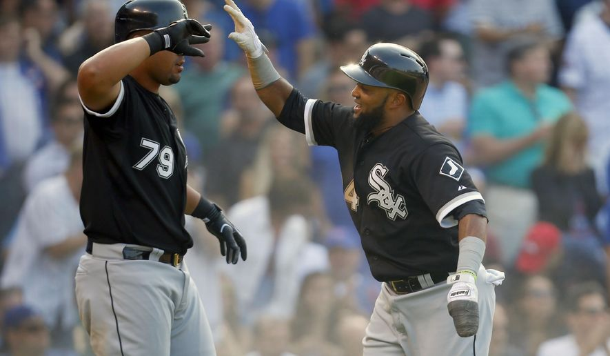 Chicago White Sox second baseman Emilio Bonifacio celebrates with teammate Jose Abreu (79) after scoring a run in the eighth inning of a baseball game against the Chicago Cubs in Chicago, on Friday, July 10, 2015.   (AP Photo/Jeff Haynes)
