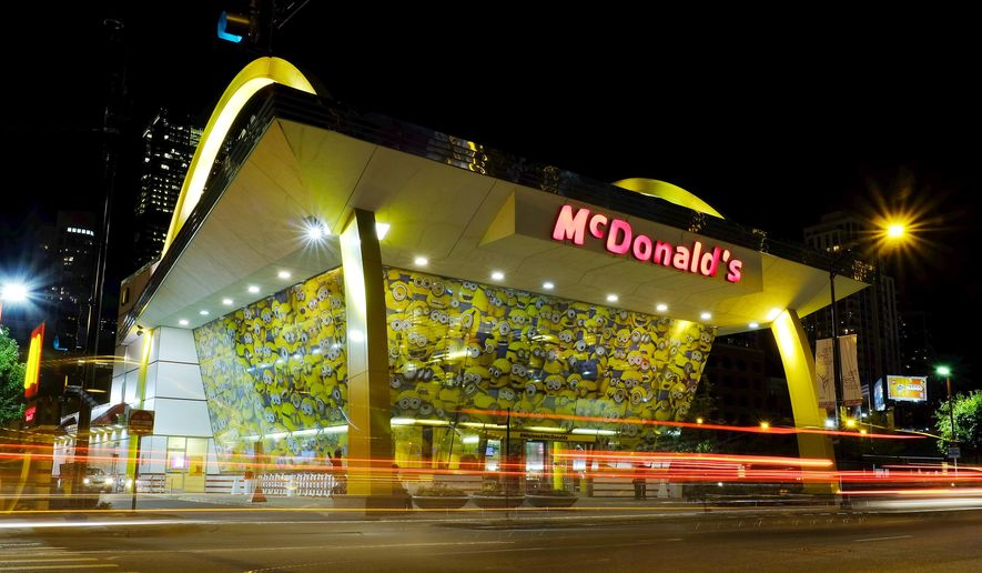 """In this July 7, 2015, photo, images of Minions adorn a McDonald's restaurant, in Chicago. McDonald's says some customers have complained that a talking toy inspired by the movie """"Minions,"""" that is included in recent Happy Meals, uses curse words. (AP Photo/Kiichiro Sato)"""