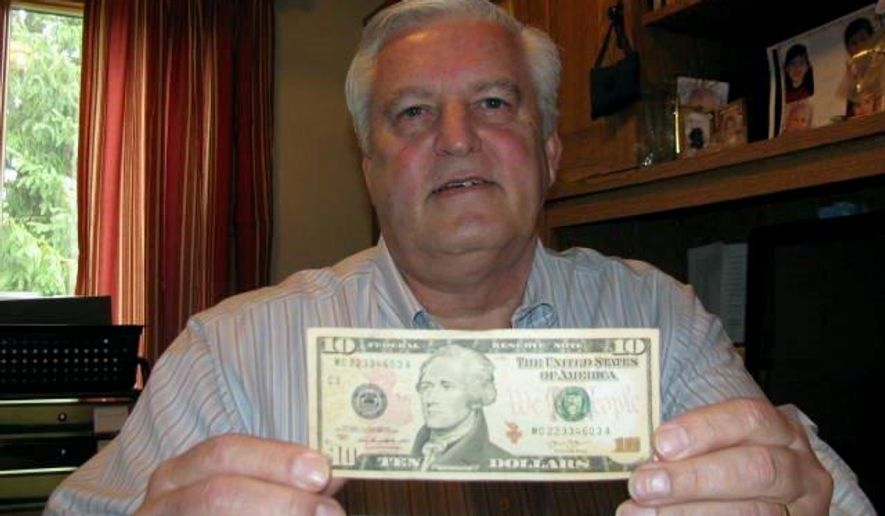 In this photo taken July 8, 2015, in Columbus, Ohio, Doug Hamilton holds a $10 bill bearing the portrait of his direct ancestor, Alexander Hamilton. Doug Hamilton and others are trying to persuade the U.S. Treasury Department to change its plan to alter the bill as part of the effort to include a portrait of a woman on paper money. (AP Photo/Mitch Stacy)