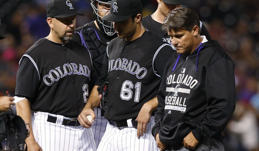 Colorado Rockies manager Walt Weiss, left, watches as relief pitcher David Hale, center, is escorted off the mound by head trainer Keith Dugger during the third inning of a baseball game against the Atlanta Braves on Thursday, July 9, 2015, in Denver. (AP Photo/David Zalubowski)