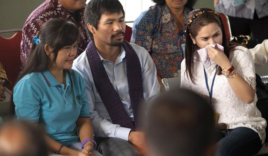 Filipino boxing icon Manny Pacquiao, center, and his wife Jinkee, right, sit with their compatriot who is currently on death row for drug offenses Mary Jane Veloso during their visit at Wirogunan Prison in Yogyakarta, Indonesia, Friday, July 10, 2015. (AP Photo)