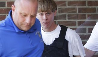 Charleston, S.C., shooting suspect Dylann Storm Roof (center) is escorted from the Shelby Police Department in Shelby, N.C., on June 18, 2015. FBI director James Comey says Roof, the gunman in the Charleston church massacre, should not have been allowed to purchase the gun used in the attack, and on July 10 attributed the problem to incomplete and inaccurate paperwork related to an arrest of Roof weeks before the shooting. (Associated Press)