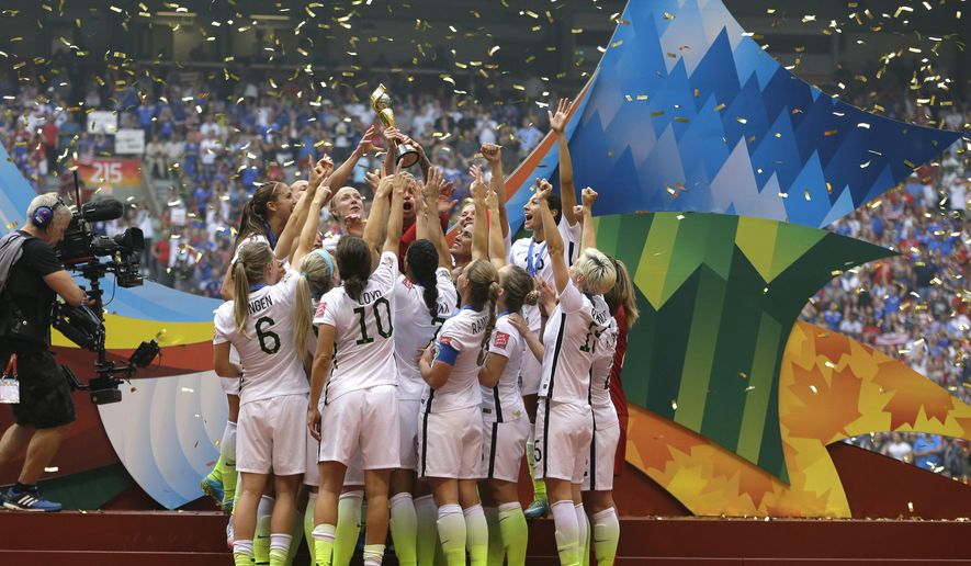 FILE - In this July 5, 2015 file photo, confetti floats down as the United States Women's National Team women celebrate with their trophy after beating Japan 5-2 in the FIFA Women's World Cup soccer championship in Vancouver, Canada. On Friday July 10, 2015,  in New York, the team will make their way through swirling ticker tape up Broadway's Canyon of Heroes to a ceremony at City Hall, where they will be the first national team since 1984 and the first all-female team ever to be honored with the iconic parade. (AP Photo/Elaine Thompson, File)