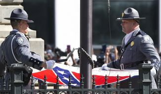 An honor guard from the South Carolina Highway patrol lowers the Confederate battle flag as it is removed from the Capitol grounds Friday, July 10, 2015, in Columbia, S.C. (AP Photo/John Bazemore)