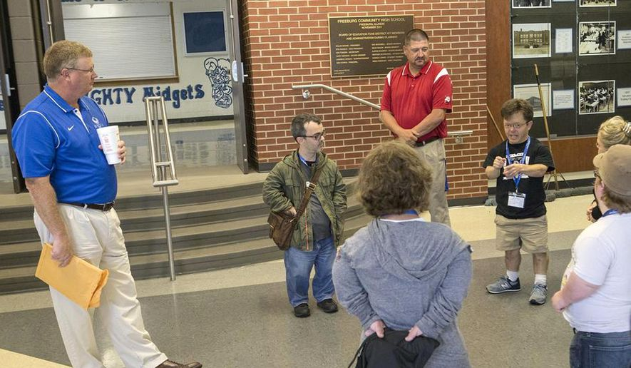 "In this July 8, 2015, photo, Freeburg school superintendent Andrew Lehman, left, listens to members of Little People of America after the group presented him with a petition requesting that Freeburg Community High School change its nickname from the ""Midgets"" during a meeting at the school in Freeburg, Ill. (Derik Holtmann/News Democrat via AP)"
